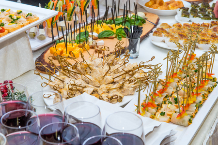 Catering table with food dishes, snacks and alcoholic and non-alcoholic drinks for guests of the event. Service at business meeting, party, weddings. Selective focus. Stock Photo