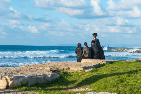 Religious Jew family sitting on the coast of Mediterranean sea in Israel and watching the waves. Sunset beach, family rest tradition. Selective focus, space for text