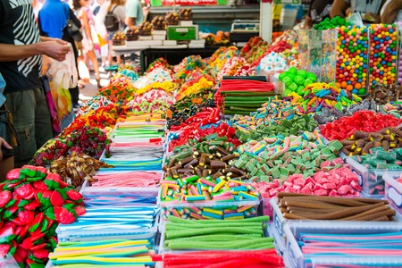 Customers choose sweets from counter with assorted colorful different shape jelly candies on market place in Tel Aviv, Israel. Selective focus, space for text