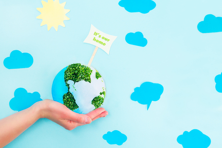 Female Hands holding Earth paper and green sprouts collage model with It's our home pointer on blue background with paper sun and clouds. Earth in your hands, Saving planet concept Imagens