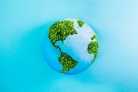 Earth model made of paper and fresh green sprouts collage on blue background. Green planet creative concept. Earth day. Selective focus, space for text