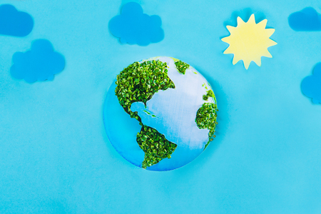 Earth model made of paper and fresh green sprouts collage on blue background with paper sun and clouds. Green planet creative concept. Earth day. Selective focus, space for text
