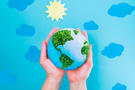 Top view Female Hands holding Earth paper and green sprouts collage model on blue background with paper sun and clouds. Earth in your hands, Saving planet concept. Space for text