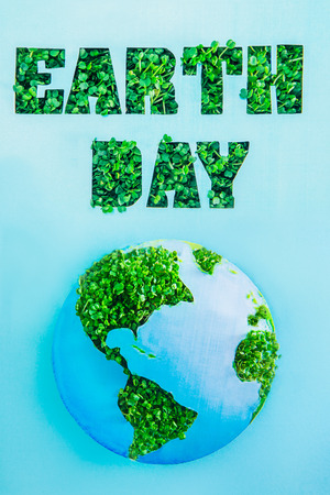 Creative concept with outline lettering Earth Day in green fresh grass sprouts and planet model on blue background. Save planet, nature. Earth Day, April 22. Space for text. Vertical