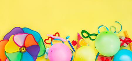 Top view bright party tools and decoration - baloons, funny carnival masks, festive tinsel on yellow background. Happy birthday greeting card. Design concept. Place for text. Wide format.