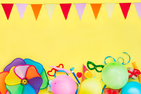 Bright yellow Festive background with party tools and decoration - baloons, funny carnival masks, festive tinsel and garland with flags. Happy birthday frame. Design concept. Place for text. Stock Photo