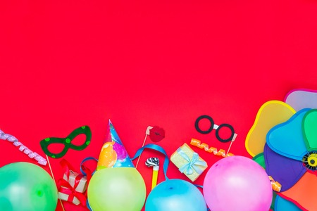 Bright red Festive background with party tools and decoration - baloons, funny carnival masks, festive tinsel. Happy birthday greeting card. Design concept. Select focus, place for text. Stock Photo