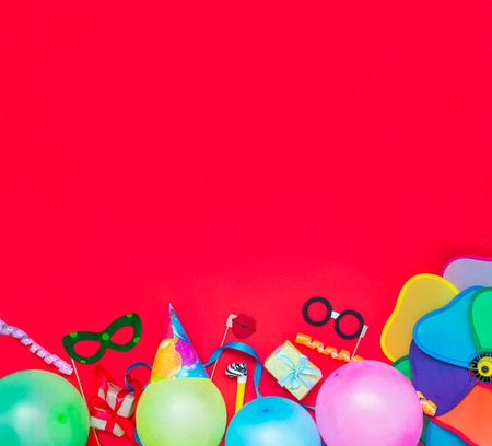 Bright red Festive background with party tools and decoration - baloons, funny carnival masks, festive tinsel. Happy birthday greeting card. Design concept. Square. Select focus, place for text. Stock Photo