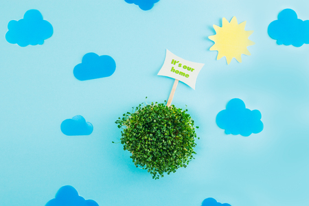Top view creative collage composition of paper sun, clouds, pointer and fresh green sprouts in round shape as model of our planet. Earth our home concept. Selective focus, space for text