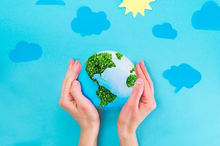 Draufsicht weibliche Hände, die Erdpapier und grünes Sprösslingscollagenmodell auf blauem Hintergrund mit Papiersonne und Wolken halten. Erde in Ihren Händen, Planetenkonzept speichernd. Platz für Text Standard-Bild