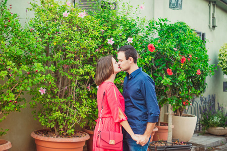 Romantic young couple in bright red and blue clothes holding hands and kissing on the street with blooming trees in pots. Love, dating, romance. Soft selective focus. Copy space