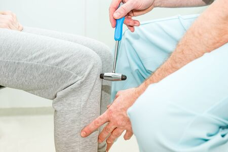 The neurologist testing knee reflex on a female patient using a hammer. Neurological physical examination. Selective focus, close up.
