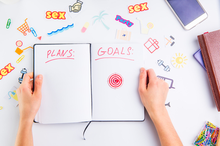 Female hands holding personal organizer with Plans and Goals headline and pushpin as arrow on target icon among other icons of actions on the working place. Concept of planning and goals achievements Stock Photo
