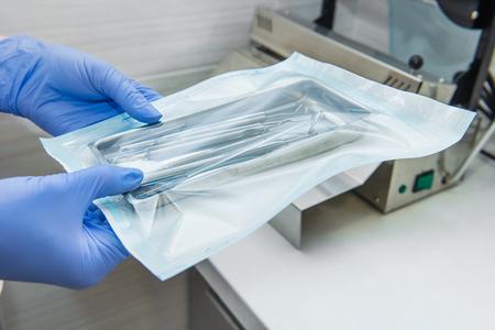 Sluit tandartsassistenten omhoog handen houdend verpakt met de medische instrumenten van de vacuümverpakkingsmachine klaar voor het steriliseren in autoclaaf. Tandartspraktijk. Selectieve focus, ruimte voor tekst.