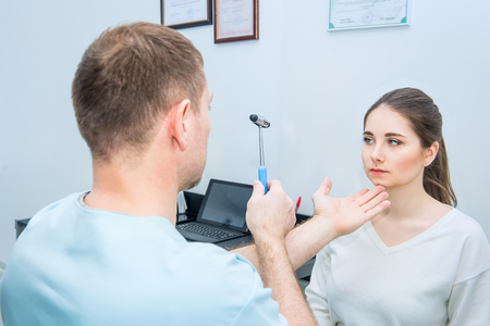 Male neurologist doctor inspecting young female patients nervous system using a hammer. Neurological physical examination. Helthcare and medicine concept. Selective focus