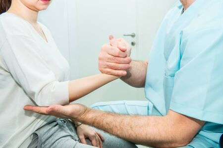 Neurological physical examination of the hands reflexes. Doctor neurologist checks the status of the patients reflexes in office in hospital. Selective focus, space for text