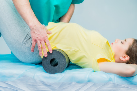 Woman at the physiotherapy doing physical exercises with her therapist, they using a massage roll. A chiropractor treats patients loins spine in medical office. Neurology, Osteopathy, chiropractic