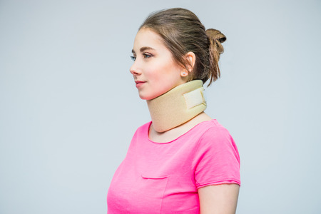 Portrait of young woman with a neck injury, osteochondrosis collar to prevent and physiotherapy. Pain treatment. Neurology, Osteopathy, chiropractic. Selective focus. space for text