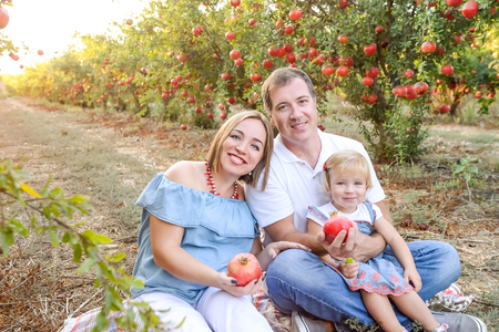 Portrait of smiling parents with baby girl daughter having rest and fun in the pomegrate fruit garden on the sunset. Happy family spending time. Sunset light. soft selective focus, space for text Stock Photo
