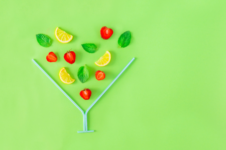 Creative layout, strawberry lemonade ingredients - lemon, mint, berries falling in coctail glass made with straws on green background. Summer drinks. Minimal food concept. Selective focus. Copy space Stockfoto
