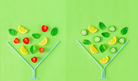 Creative layout. Strawberry and cucumber lemonade ingredients, lemon, mint falling in coctail glass made with straws on green background. Summer drinks. Duplex. Minimal food concept. Copy space Stockfoto
