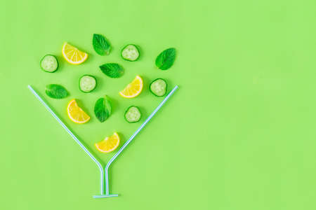 Creative layout of lemonade ingredients - lemon, mint, cucumber slices falling in coctail glass made with straws on green background. Summer drinks. Minimal food concept. Selective focus. Copy space