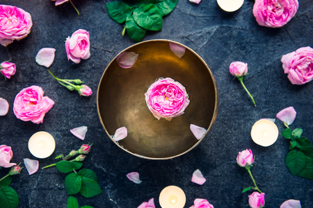 Tibetan singing bowl with floating rose inside. Burning candles, tea rose flowers and petals on the black stone background. Meditation and Relax. Exotic massage, spa procedure. Selective focus Standard-Bild
