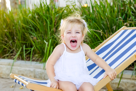 Close up portrait of cute emotional blondy toddler girl in white dress sitting on the deckchair and yelling. City park recreation area. Selective focus, copy space