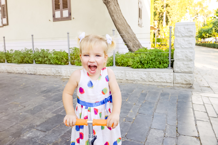 Cute little emotional blondy toddler girl in dress looking at camera and riding scooter in the city park recreation area with buildings and trees. Active leisure in city. Kid's sport. Copy space Banco de Imagens