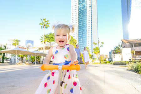 Emotional cute little blondy toddler girl in dress riding scooter in the city park recreation area with modern skyscraper buildings on the background. Active leisure time. Kid's sport. Copy space