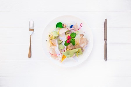 Top view served with knife and fork plate with unreal salad from recycle waste, synthetic ingredients. Concept of artificial, food. GMO, E numbers . Use of chemicals in the food industry. Copy space. Stok Fotoğraf