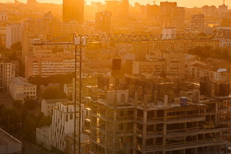 Construction crane and buildings under construction in urban city scape in back sunset light.