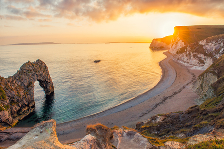 Landscape of empty Durdle Door beach at sunset.