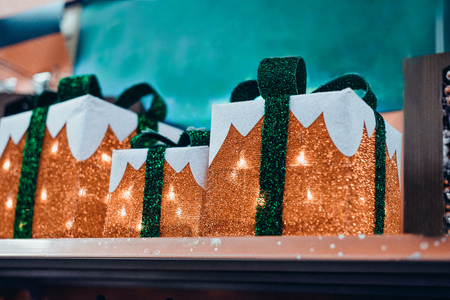 Golden Christmas and new year illumination in shape of Gift boxes with a green bow. Christmas background, Christmastime celebration. Winter holiday and xmas. Soft elective focus. copy space