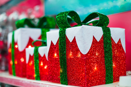 Christmas and new year illumination in shape of red Gift boxes with a green bow. Christmas background, Christmastime celebration. Winter holiday and xmas. Soft elective focus. copy space