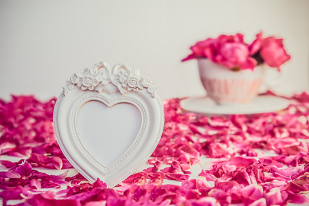 Heart shaped vintage style blank photoframe on the white table with fresh petals and bouquet of pink purple peonies in cup.