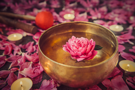 Tibetan singing bowl with floating inside in water pink peony flower. Burning candles, special sticks and petals on the black stone background.