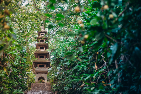 Five-story stone pagoda standing on the top of hill among green trees in japanese garden. Traditional japan exterior design, outdoor decor. Relax and mind calm concept. Selective focus. Copy space Editorial