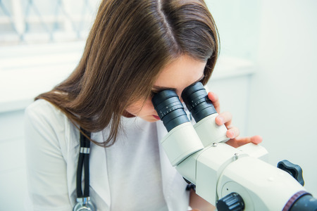 Close up woman gynecologist working with colposcope and makes microscopic investigation in clinic. Selective focus, copy space Stock Photo