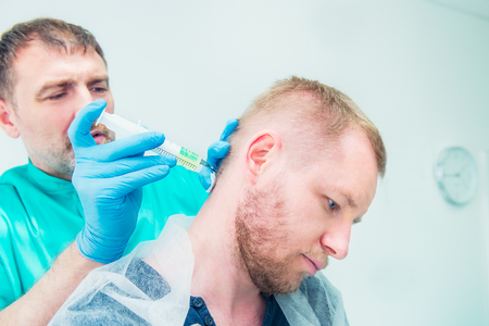 Close up Neurologist doctor makes an injection therapy (blockade) into head nape muscle of male patient. Alternative pain treatment concept. Selective focus, space for text. Stock Photo