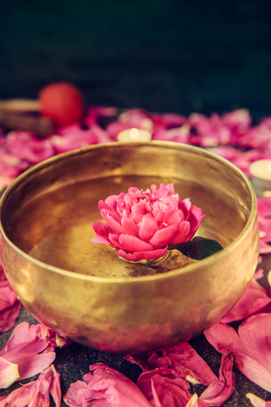 Tibetan singing bowl with floating in water pink peony flower. Burning candles and petals on the black stone background. Meditation and Relax. Exotic massage. Vertical. Selective focus. Copy space