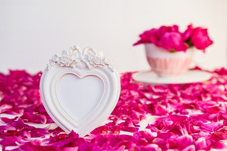 Heart shaped vintage style blank photoframe on the white table with fresh petals and bouquet of pink purple peonies in cup. Love, romantic, Valentines day concept. Selective focus. Copy space