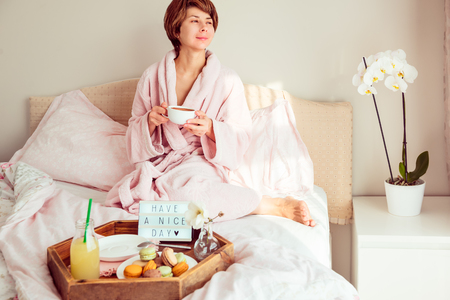 Good morning mood. Young woman in bathrobe sitting on the bed, drinking coffee and has her breakfast in bed with Have a nice day text on lighted box. Hospitality, care, service concept. Copy space