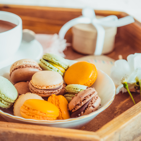 Sweet breakfast in bed for lover. Close up macaroons, cup of coffee, flower and gift box on wooden tray. Romantic breakfast in bed. Birthday, Valentine's day morning. Square card. Selective focus Archivio Fotografico