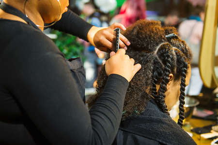 Close up african hairstylist braided hair of afro american female client in the barber salon. Black healthy hair culture and Style. Stylish therapy professional care concept. Selective focus Foto de archivo