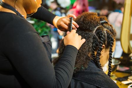 Nahaufnahme des afrikanischen Friseurs geflochtenes Haar der afroamerikanischen Kundin im Friseursalon. Schwarze gesunde Haarkultur und Stil. Stilvolles therapeutisches professionelles Pflegekonzept. Selektiver Fokus
