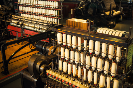 Rows of white cotton threads on vintage automatic loom. The concept of historical development of weaving in England. Selective focus. Copy space