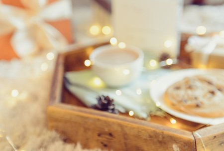 Blurred Christmas and New Year background. Composition with Cocoa, cookies, little giftbox and postcard on the wooden tray. Sweets for Santa. Festive breakfast. Winter Holidays