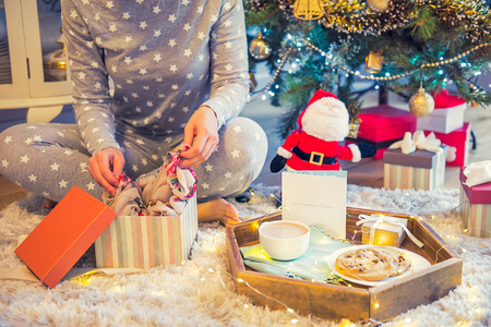 No face young woman opening Christmas present box with blurred wooden tray with festive breakfast. Cocoa and cookies for Santa. Christmas and New Year background. Soft selective focus. Vintage tonning.