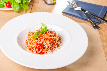 Fresh, cooked Italian spaghetti, pasta with marinara or tomato sauce decorated with basil on the white plate served on the wooden table with catlery. Selective focus, copy space